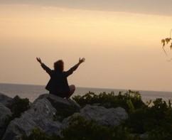 Claudie les bras dans les air au bord de la mer.