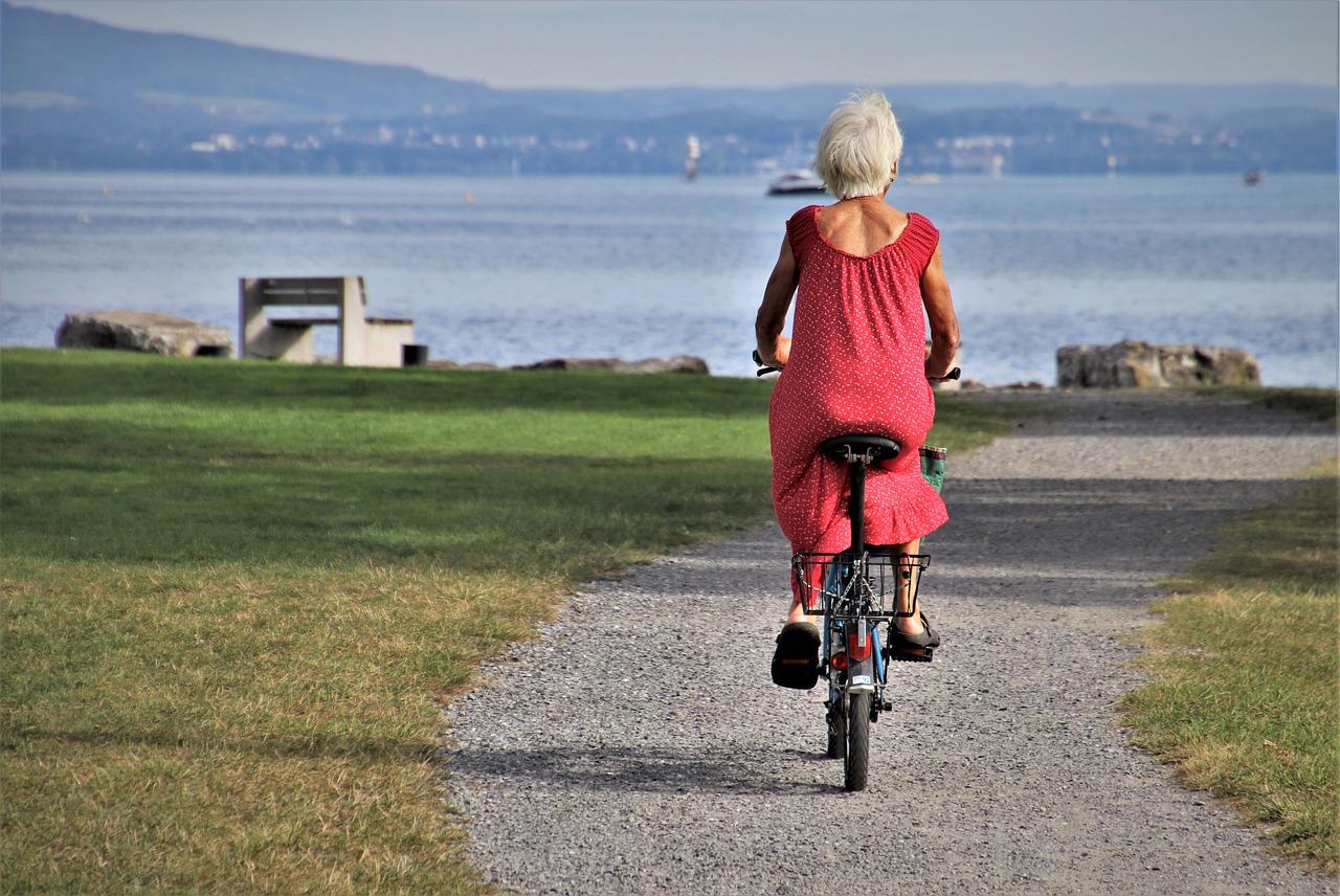 Femme âgée en vélo sur chemin.