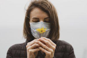 Personne portant le masque et tenent une fleur.