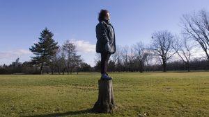Claudie debout sur un tronc d'arbre.