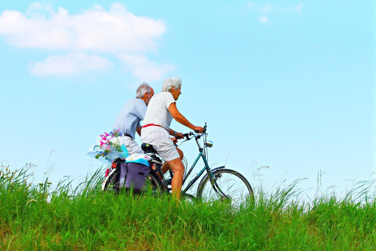 Un couple de personnes âgées faisant du vélo.